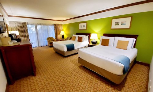 The Inside of the Resort/City view room with two queen beds, balcony in the background.